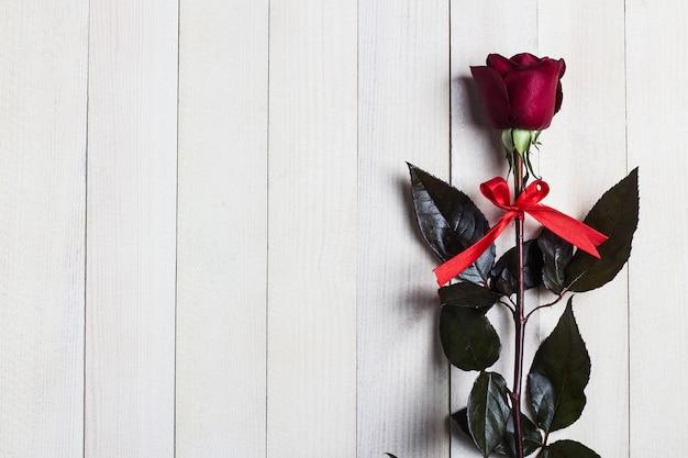 La sorpresa del regalo della rosa rossa del giorno delle madri delle donne di giorno di biglietti di s. valentino su legno bianco