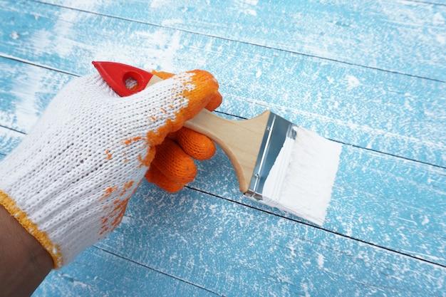 La spazzola della holding della mano del pittore dipinge il legno blu