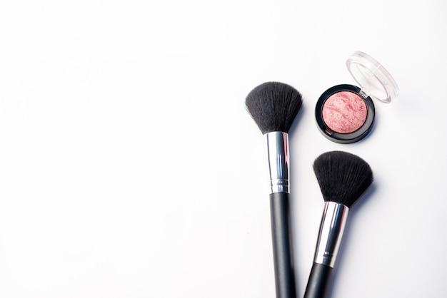 La spazzola di trucco e arrossisce su una priorità bassa bianca. concetto di bellezza. close-up con spazio per il testo