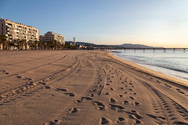 La spiaggia di badalona all'alba con impronte e tracce di auto sulla sabbia