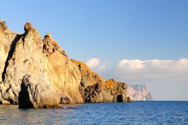 La spiaggia rocciosa è bagnata da calme onde del mare