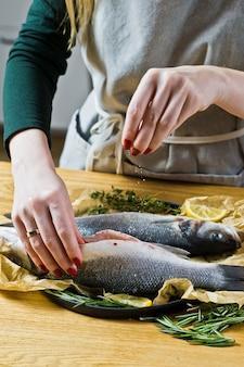 La spigola salata dello chef su una tavola di legno.