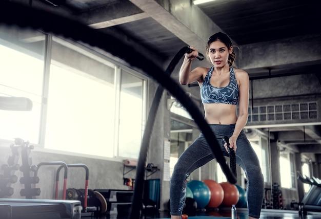 La sportiva asiatica misura l'addestramento con la corda di battaglia nella palestra di forma fisica. sport e allenamento motivati