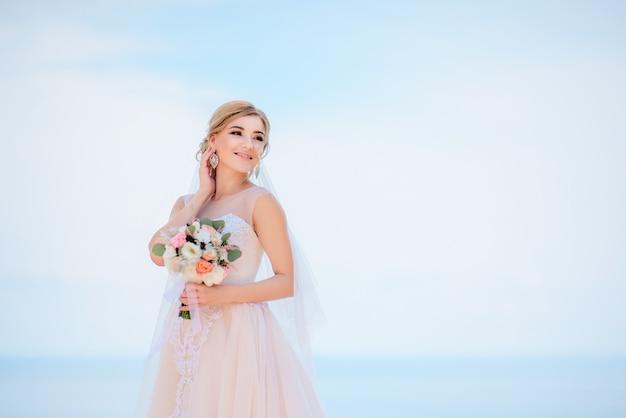 La sposa affascinante in vestito da pesca sorride posare prima di una grande vista del mare in un giorno soleggiato