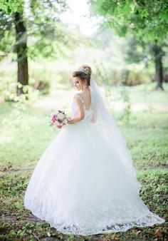 La sposa affascinante posa con il mazzo variopinto di nozze nel parco