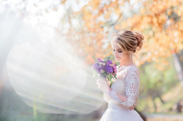 La sposa affascinante posa con il mazzo viola di nozze sul prato verde