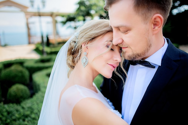 La sposa bionda tenera si appoggia alla spalla dello sposo che sta nel giardino verde dell'estate