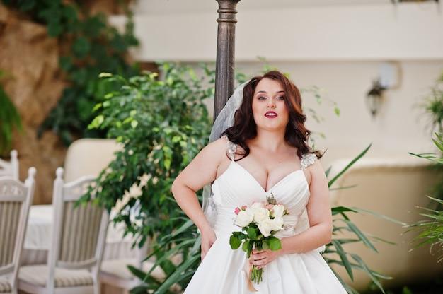 La sposa castana dei grandi seni con il mazzo di nozze ha posato alla lanterna del fondo della sala per matrimoni