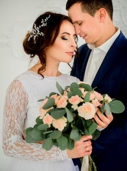La sposa con la ghirlanda d'argento tra i capelli si appoggia allo sposo tenero con bouquet di rose beige