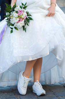 La sposa con un mazzo di cerimonia nuziale si è vestita in un vestito bianco che mostra le scarpe da tennis sulle sue gambe.