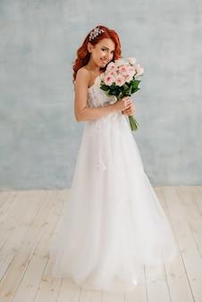 La sposa dai capelli rossi felice sta con il mazzo in sue mani