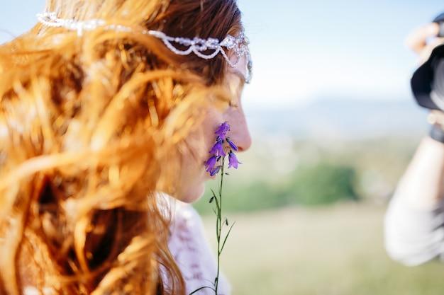 La sposa dai capelli rosso dorato si appoggia a un minuscolo fiore viola