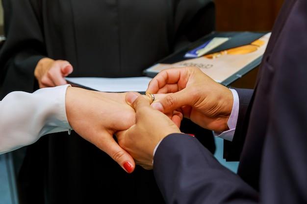 La sposa di bellezza e lo sposo bello stanno indossando gli anelli l'un l'altro.