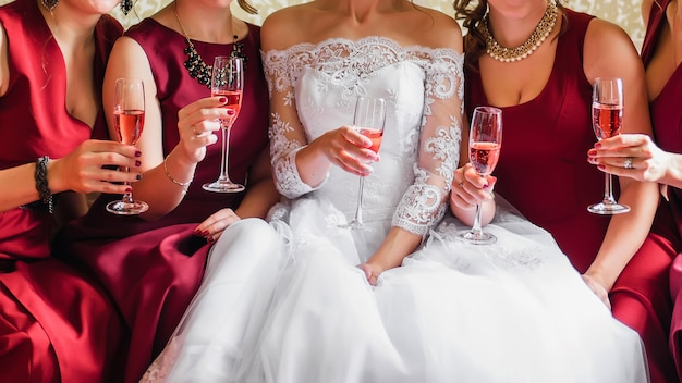 La sposa e le amiche felici con i bicchieri di vino in mano tintinnano e festeggiano