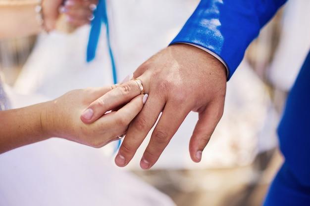 La sposa e lo sposo accanto a, l'abito da sposa anello nuziale allo sposo, mano maschile e femminile con fedi nuziali, cerimonia nuziale, insieme per sempre, tempo, felicità, anelli di scambio