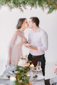 La sposa e lo sposo baciano e mangiano la torta nuziale decorata con pino, bacche e fiori di cotone con le loro damigelle e groomsmen