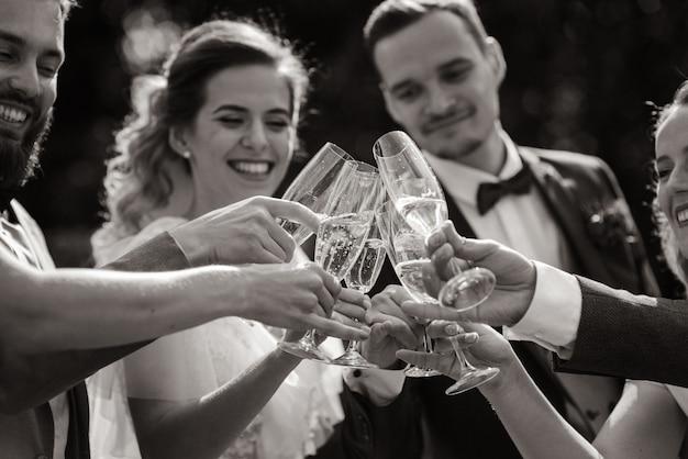La sposa e lo sposo bevono champagne con i migliori amici all'aperto con sorrisi sinceri, vista monocromatica