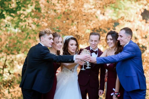 La sposa e lo sposo con i migliori amici stanno bevendo champagne nella foresta con alberi ingialliti in una calda giornata di sole