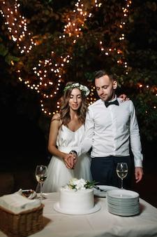 La sposa e lo sposo felici hanno tagliato la torta nuziale nella decorazione leggera anteriore della ghirlanda.