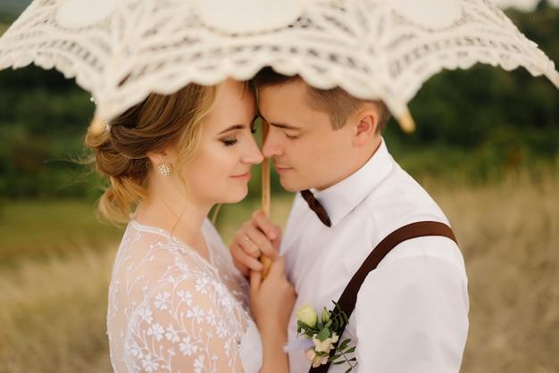 La sposa e lo sposo felici si abbracciano e tengono un ombrello d'annata sulla natura. avvicinamento. nozze, concetto di amore.