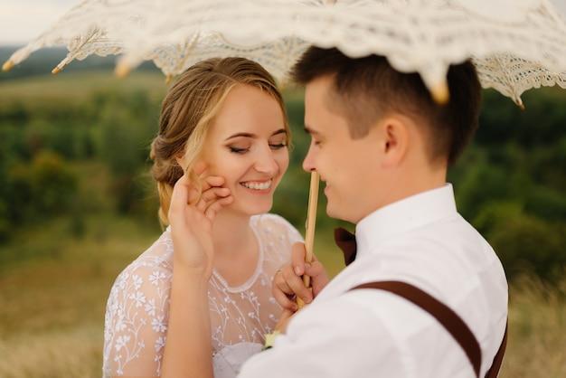 La sposa e lo sposo felici si sposano e tengono un ombrello d'annata sulla natura