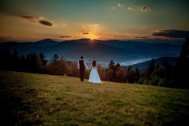 La sposa e lo sposo guardano il tramonto che sta su una collina
