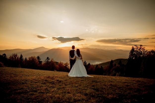La sposa e lo sposo guardano il tramonto che sta sulla collina