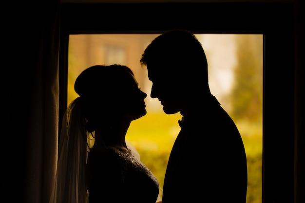La sposa e lo sposo in una casa accogliente, foto scattata con luce naturale dalla finestra.