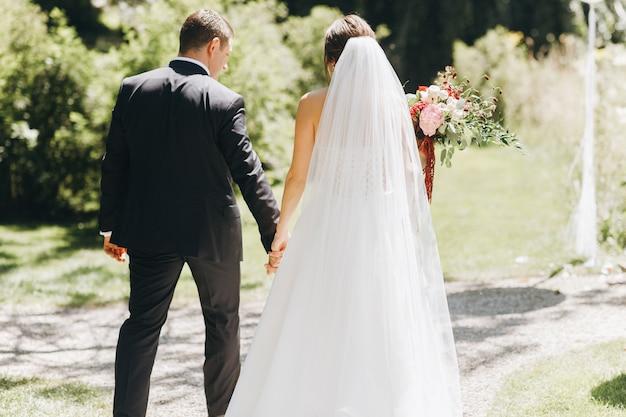 La sposa e lo sposo si tengono per mano davanti all'arco