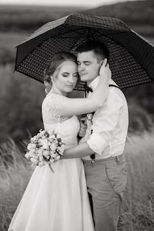 La sposa e lo sposo sono in piedi contro il bellissimo paesaggio con un ombrello.