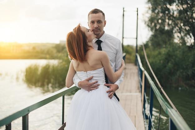 La sposa e lo sposo sono in piedi sul ponte