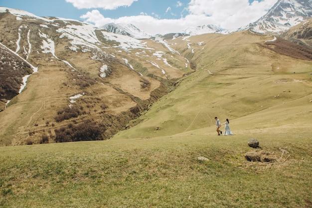La sposa e lo sposo stanno camminando sull'erba in estate in alta montagna