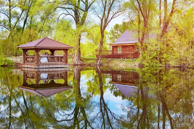 La sposa e lo sposo stanno in un gazebo in legno sul lago. gli alberi primaverili si riflettono nell'acqua