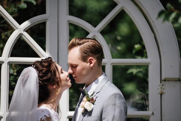 La sposa e lo sposo stanno sullo sfondo di un arco bianco traforato. cerimonia nuziale nella foresta. si tengono per mano e si guardano.