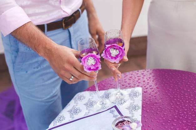 La sposa e lo sposo stanno tenendo i bicchieri di champagne