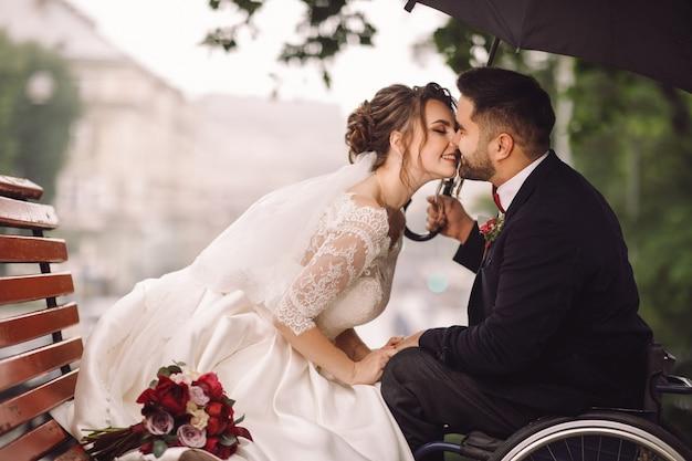 La sposa e lo sposo sulla sedia a rotelle si siedono baciare sulla panchina nel parco