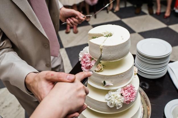 La sposa e lo sposo tagliare la torta nuziale in un banchetto in un ristorante