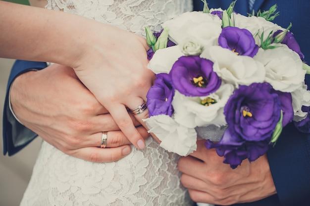 La sposa e lo sposo tengono le loro mani con gli anelli sopra un mazzo di nozze con i fiori blu e bianchi
