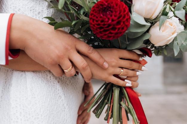 La sposa e lo sposo tengono ricco bouquet da sposa rosso tra le loro braccia