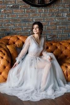 La sposa è una bruna dall'aspetto europeo. ritratto singolo. trucco e acconciatura da sposa. mattina della sposa boudoir in hotel.