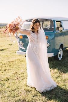 La sposa felice che porta un vestito rosa con il bouqet di nozze sta ballando vicino alla retro-automobile