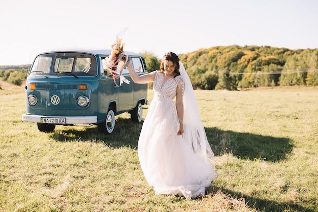 La sposa felice con il mazzo sta ballando vicino alla retro-automobile