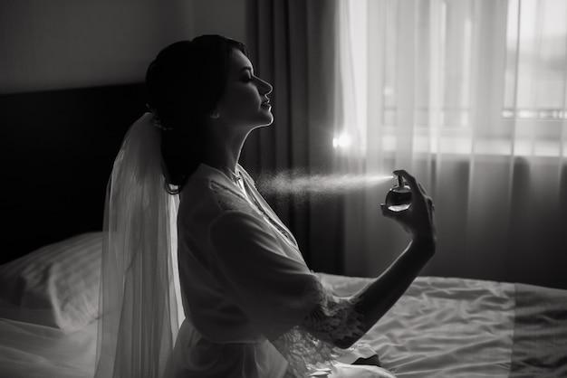 La sposa felice spruzza un profumo. preparazione del mattino di nozze. ritratto della sposa alla mattina delle nozze.