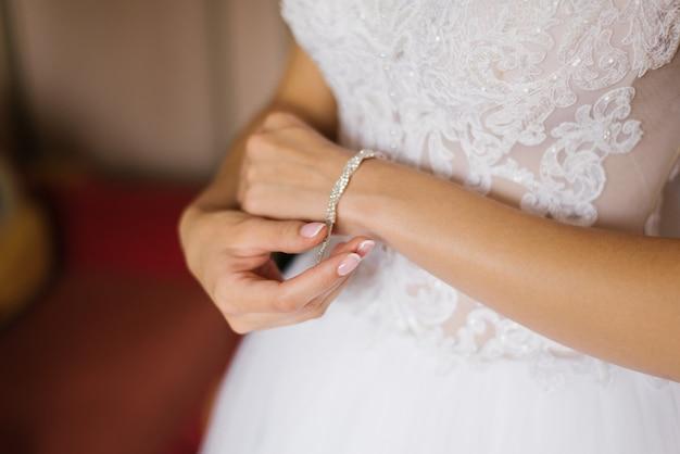 La sposa fissa il braccialetto sulla sua mano