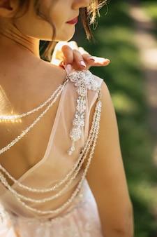 La sposa guarda la spalla con le perline