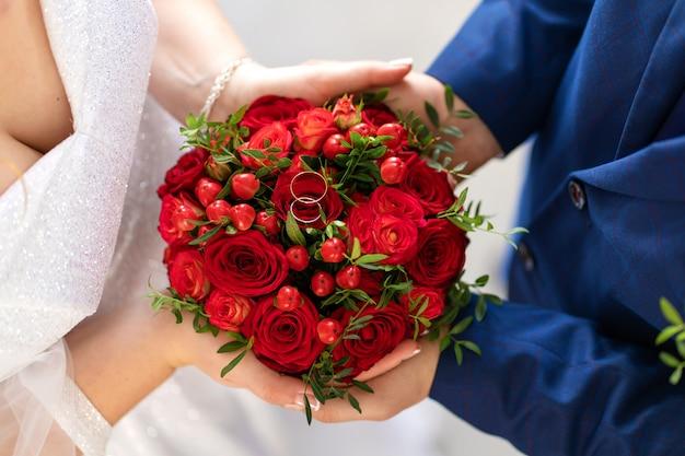 La sposa in abito bianco e lo sposo tengono in mano un elegante bouquet da sposa di rose rosse. dettagli del matrimonio.