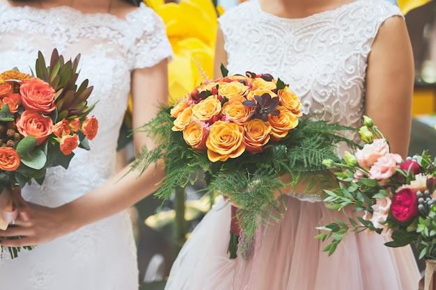 La sposa in abito bianco tiene tra le mani un bellissimo bouquet da sposa di rose arancioni