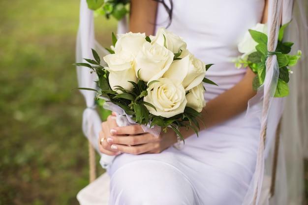 La sposa in possesso di un mazzo di rose bianche