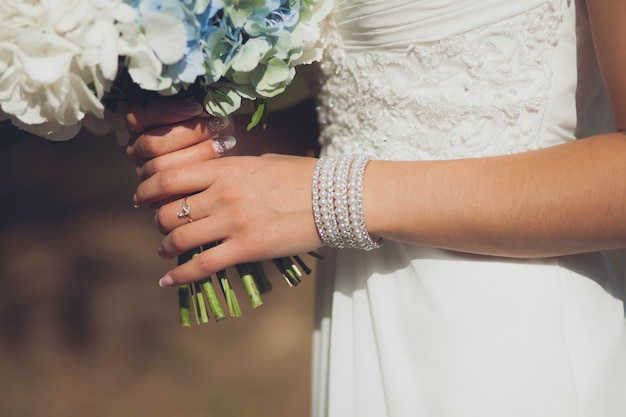 La sposa in un abito da sposa bianco elegante è in possesso di un bellissimo bouquet da sposa di diversi fiori e foglie verdi. tema del matrimonio