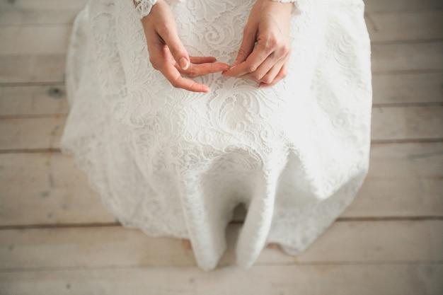 La sposa in un abito da sposa bianco, traforato.